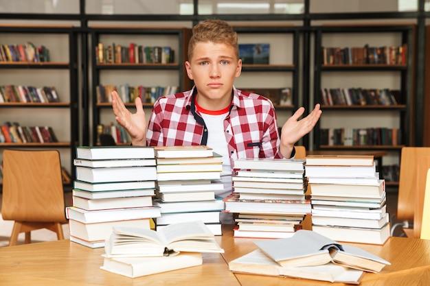 Adolescente confuso che si siede alla biblioteca