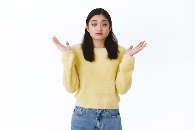 Ragazza asiatica confusa e inconsapevole allarga le mani di lato e scrolla le spalle come non so, non posso dirlo, non essere in grado di rispondere come privo di informazioni, stare in piedi perplesso o indeciso, non posso fare una scelta