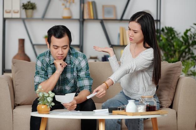 Giovane donna infelice confusa che mostra mucchio di fatture non pagate al fidanzato pensieroso