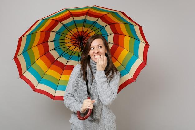 Donna confusa in maglione grigio, sciarpa alzando lo sguardo, rosicchiando unghie, tenere ombrello colorato isolato su sfondo grigio. emozioni della gente di stile di vita sano di modo, concetto di stagione fredda. mock up copia spazio.