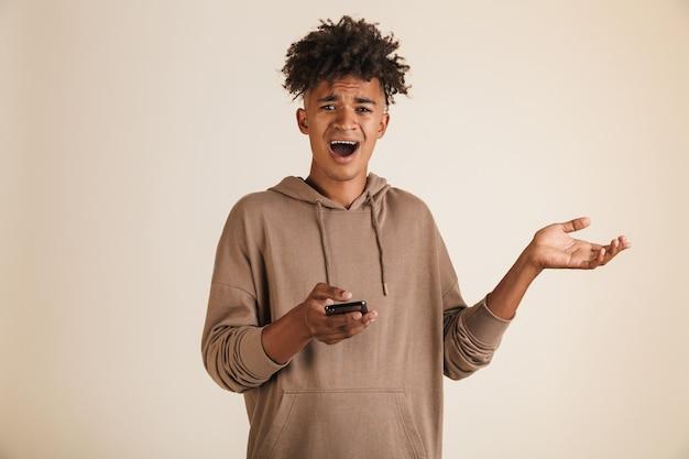 Confuso giovane afroamericano che utilizza il telefono cellulare