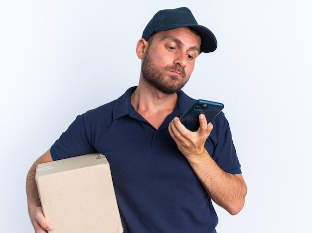 Confuso giovane fattorino caucasico in uniforme blu e cappuccio che tiene scatola di cartone e telefono cellulare guardando il telefono cellulare isolato sul muro bianco