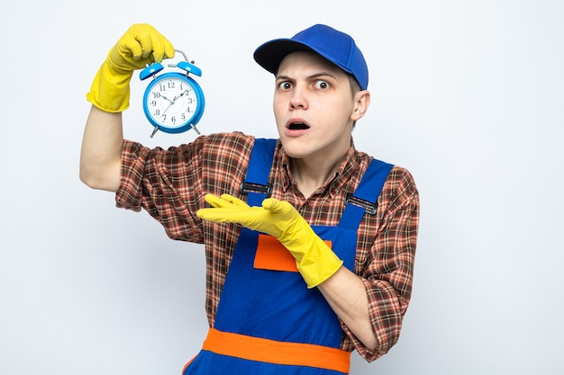Giovane addetto alle pulizie confuso che indossa uniforme e berretto con guanti che tengono e punta con la mano alla sveglia