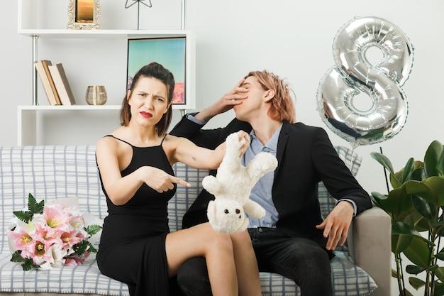 Confuso giovane coppia il giorno delle donne felici ragazza che tiene e punti a orsacchiotto ragazzo volto coperto con la mano seduto sul divano nel soggiorno