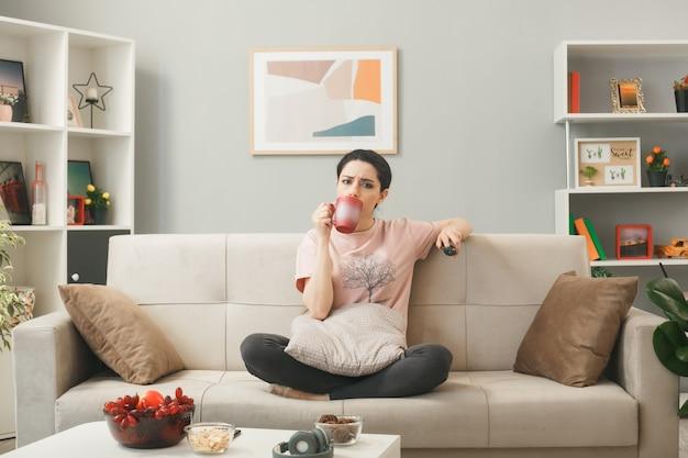 Ragazza confusa che tiene il telecomando della tv con una tazza di tè seduta sul divano dietro il tavolino da caffè in soggiorno