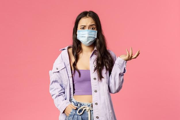 La ragazza confusa che scrolla le spalle, sembra non capire perché la gente esca durante l'epidemia di pandemia da coronavirus