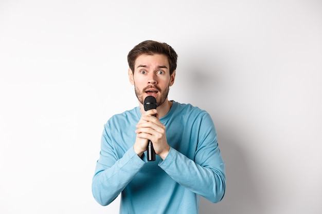 Giovane confuso che guarda nervosamente la macchina fotografica mentre canta al karaoke, tenendo il microfono, in piedi su sfondo bianco.