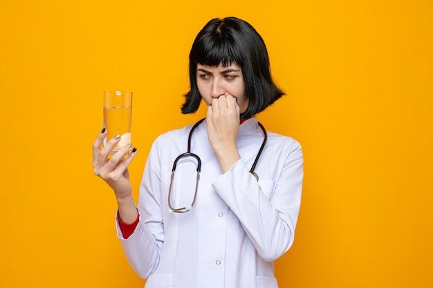 Confusa giovane bella ragazza caucasica in uniforme da medico con stetoscopio che tiene in mano e guarda un bicchiere d'acqua che si morde le unghie
