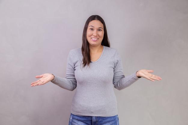 Confuso giovane donna su sfondo grigio con spazio per il testo. donna che tiene le mani dicendo che non sa isolato su sfondo grigio. non ho idea del concetto