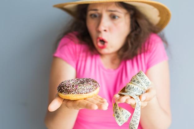 Giovane donna confusa che tiene una ciambella e un nastro di misurazione. concetto di dolci, cibo spazzatura malsano e obesità.