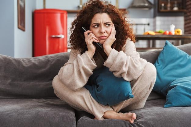 Confuso giovane donna che indossa abiti da casa seduta sul divano in appartamento e tenendo il telecomando