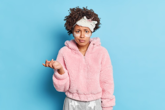La giovane donna confusa con i capelli ricci indossa la maschera da notte solleva il palmo esitante applica cerotti di collagene sotto gli occhi per ridurre le rughe isolate sul muro blu