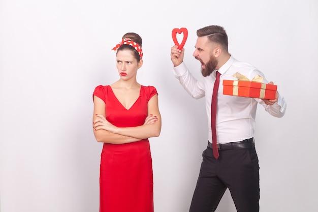 Conflitto. la donna ignora l'uomo, il ruggito dell'uomo d'affari, il regalo in mano e il cuore. indoor, girato in studio, isolato su sfondo grigio