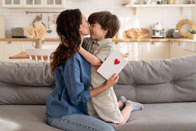 Congratulazioni per la festa della mamma mamma felice che abbraccia un bacio piccolo figlio in età prescolare tiene un biglietto di auguri fatto a mano