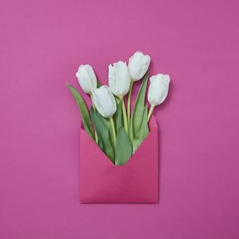 Cartolina di congratulazioni di busta artigianale di tulipani bianchi su uno sfondo viola con posto per il testo. lay piatto.