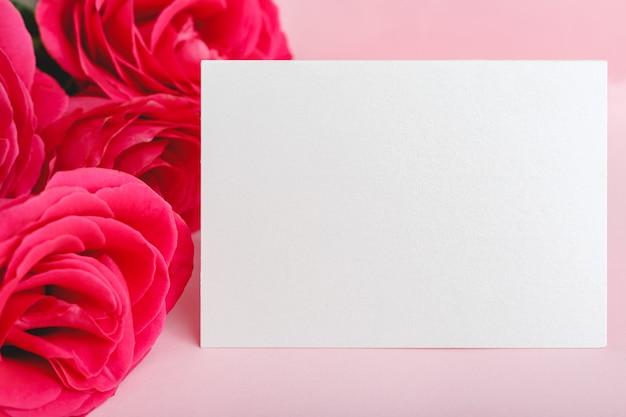 Biglietto di congratulazioni in bouquet di rose rosse rosa su sfondo rosa.