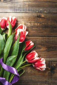 Per congratulazioni, biglietti di auguri. i tulipani freschi della molla fiorisce, su un copyspace di legno di vista superiore