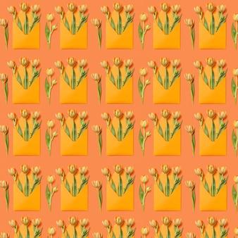 Modello di congratulazioni con mazzi di tulipani in buste su uno sfondo arancione. cartolina d'auguri.