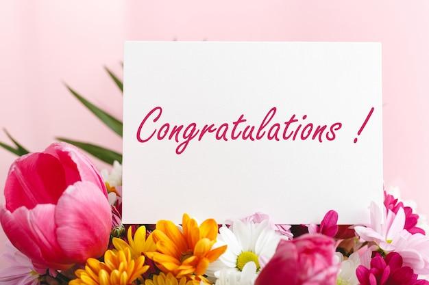 Testo di congratulazioni su carta regalo in bouquet di fiori su sfondo rosa. scheda vuota bianca con spazio per testo, mockup di cornice. concetto di fiore festivo di primavera, carta regalo.