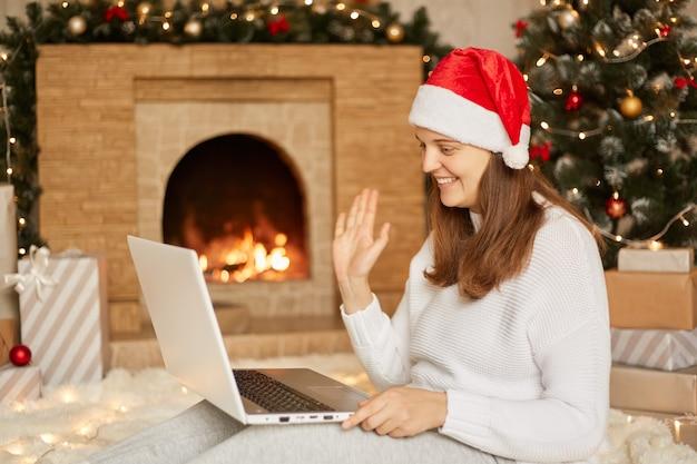 Congratulazioni via internet. ragazza sorridente a casa utilizzando notebook computer portatile per videochiamata, donna che guarda la fotocamera e agitando le mani di saluto, essendo felice, seduto sul pavimento con il computer portatile sulle ginocchia.