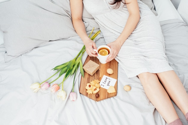 Congratulazioni alla tua amata donna a san valentino. colazione a letto per una ragazza in camicia da notte. fiori e un regalo per il 14 febbraio.