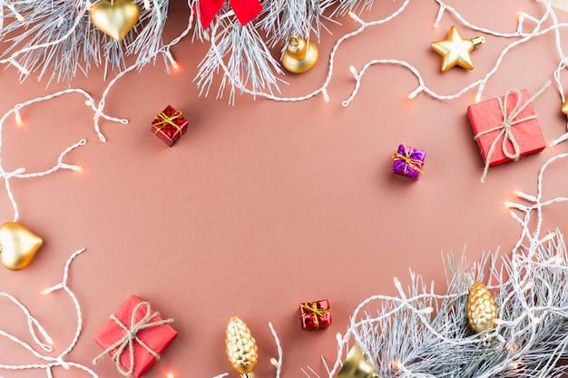 Coni di conifere, fiocchi di neve, regali e luci di natale su uno sfondo caldo