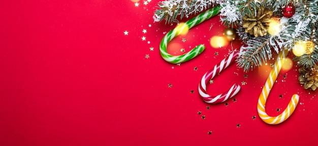I rami di conifere hanno decorato il bastoncino di zucchero di natale su fondo rosso