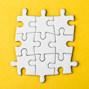 Pezzi di puzzle in bianco collegati isolati su una superficie gialla