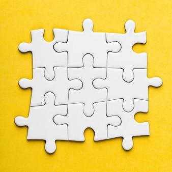 Pezzi di puzzle in bianco collegati su uno sfondo giallo. foto di concetto