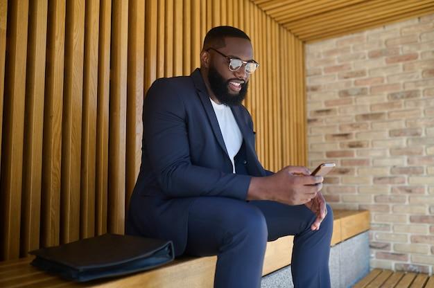Collegato. un uomo dalla pelle scura in completo seduto su una panchina con uno smartphone in mano
