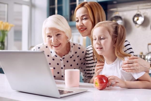 Connettersi con i più cari. adorabile bambina seduta al bancone della cucina con la nonna e la madre, e tutti insieme fanno una videochiamata tramite laptop