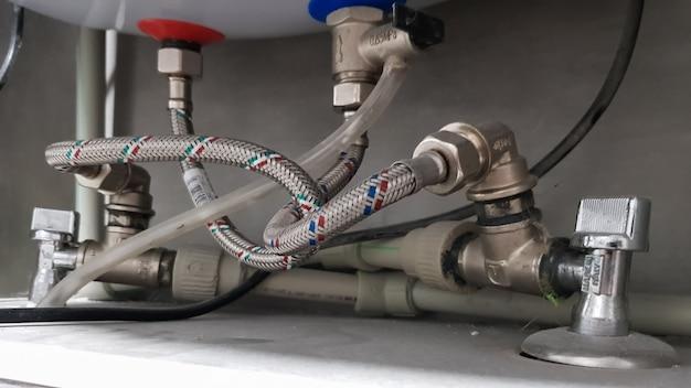 Collegamento della rete idrica, acqua calda e fredda alla caldaia. tubo per acqua calda e fredda in bagno. collegamenti idraulici per uno scaldacqua elettrico domestico.