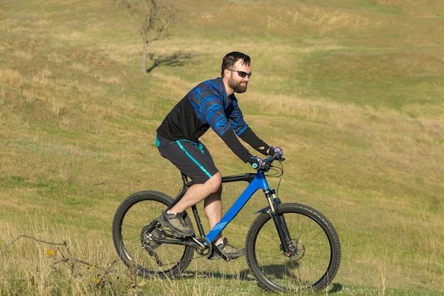 Conquista delle vette da ciclista in pantaloncini e maglia su una moderna bici hardtail in carbonio