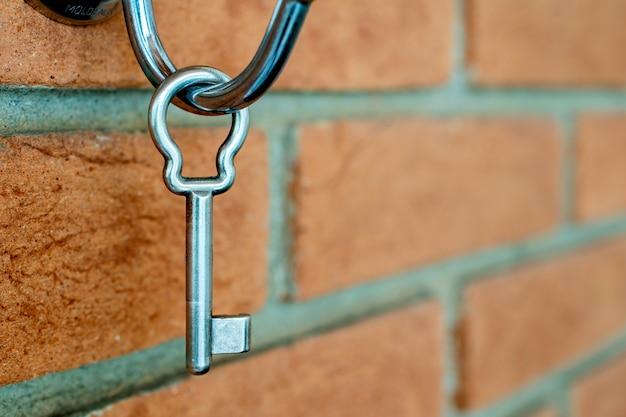 Conquista della proprietà della casa. chiave sul muro di mattoni.