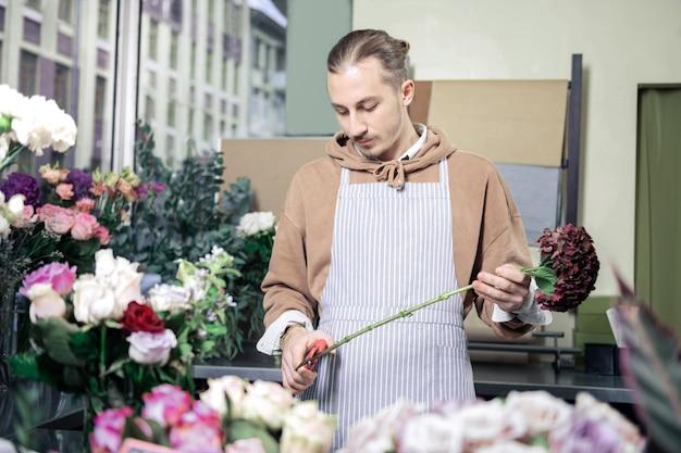 Lavoratore cosciente. fiorista competente che taglia il gambo mentre va a comporre ikebana