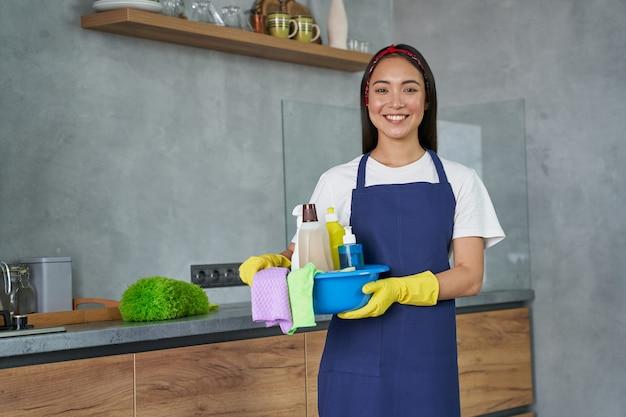 Consideralo pulito e felice, giovane donna delle pulizie che sorride alla telecamera tenendo il contenitore pieno di