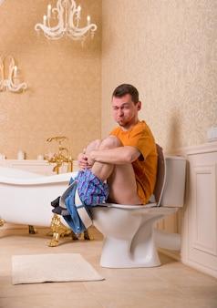 Concetto di problema di costipazione. uomo con i pantaloni abbassati seduto sulla tazza del water