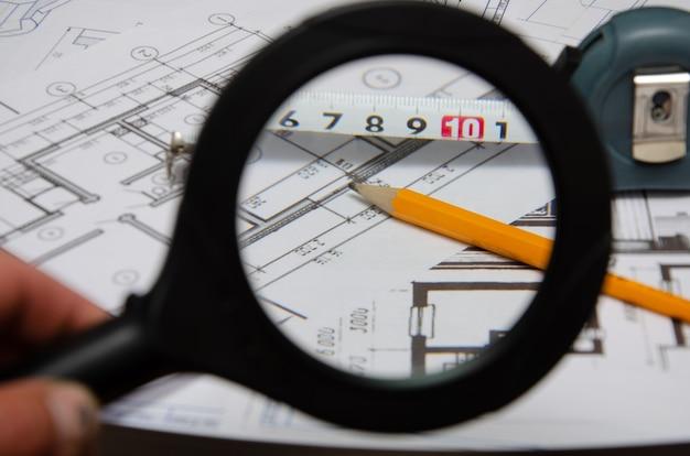 Costruzione del layout dell'edificio, finanziamento della costruzione, pacchi di dollari, disegno dell'edificio su carta, disegni arrotolati in un rotolo.