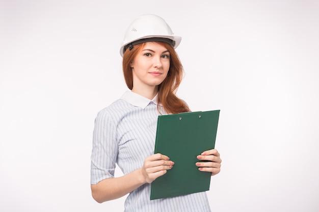 Concetto di costruzione, edificio e lavoratori. bella donna ingegnere azienda verde clip board sopra