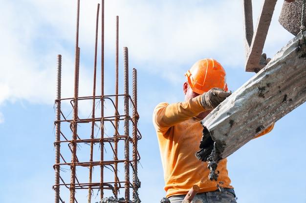 Lavoratori edili in cantiere versando calcestruzzo in forma, uomo che lavora in altezza con cielo blu in cantiere