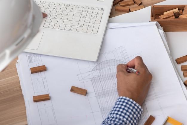 Concetto della costruzione, mani dell'ingegnere che lavorano al modello