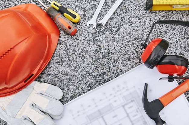 Vista dall'alto del concetto di costruzione di un set di strumenti professionali per indumenti da lavoro di sicurezza e disegno di costruzione