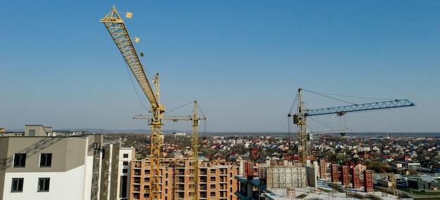 Costruzione e costruzione di grattacieli, industria delle costruzioni con attrezzature di lavoro e lavoratori. vista dall'alto, dall'alto.