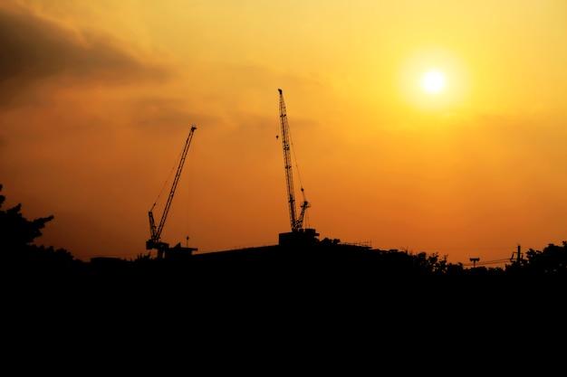 Gru di costruzione il giorno con il cielo al crepuscolo