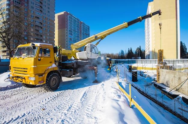 Una gru da cantiere lavora in un cantiere con un carico