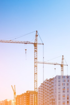 Gru edili ed edifici contro il cielo, foto verticale tonica