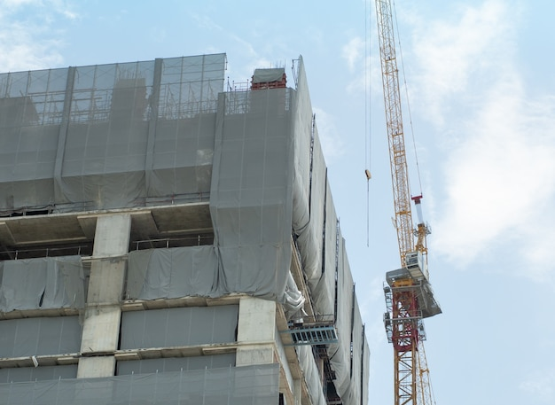 Le gru edili e gli edifici da costruzione sono avvolti in una tela antipolvere per garantire la sicurezza