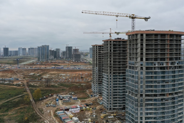 Gru edili in piedi vicino a edifici a più piani