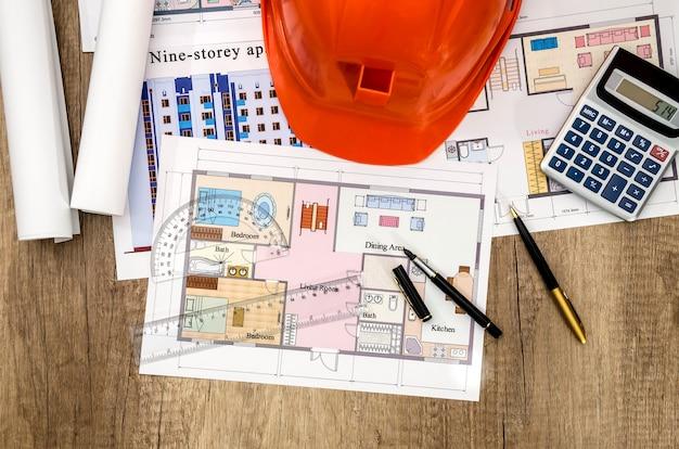 Disegno di costruzione con una calcolatrice e un casco sul tavolo