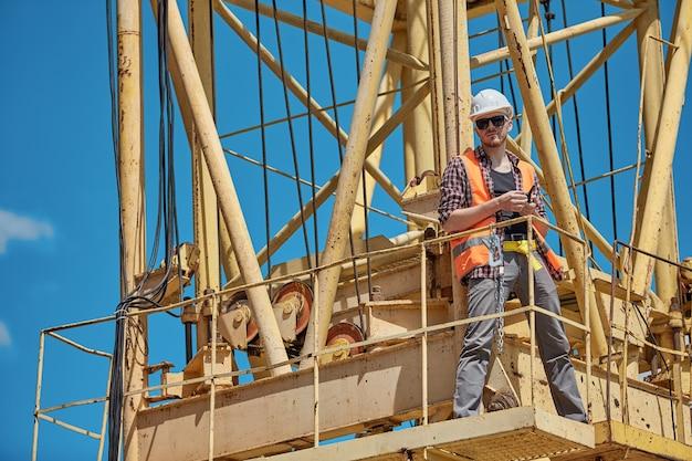 Un ingegnere edile con una camicia a quadri, un giubbotto arancione e un elmetto bianco su una gru gialla con un walkie-talkie in mano. caposquadra, supervisore, operaio